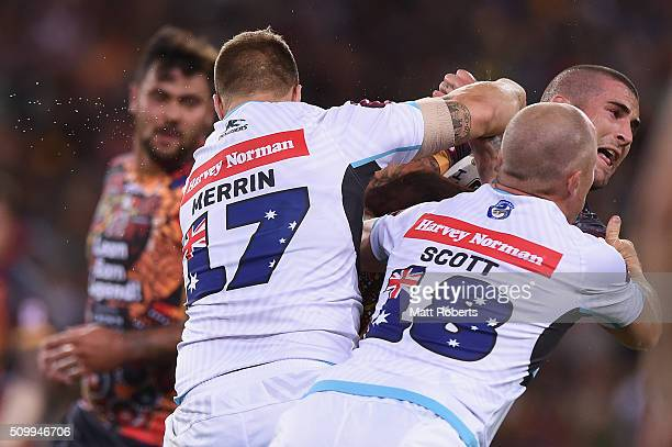 Joel Thompson of the Indigenous All Stars is tackled by Trent Merrin and Beau Scott of the World All Stars during the NRL match between the...