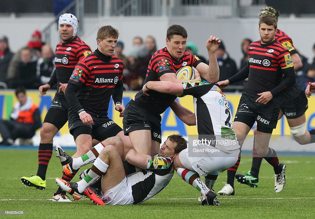 Joel Tomkins of Saracens is held by NIck Evans and Joe Gray during the Aviva Premiership match between Saracens and Harlequins at Allianz Park on March 24, 2013 in Barnet, England.