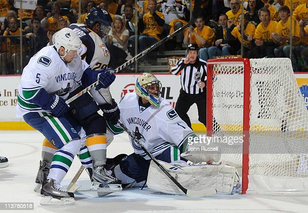 Joel Ward of the Nashville Predators gets the puck in the net against Roberto Luongo of the Vancouver Canucks as Christian Ehrhoff defends in Game...