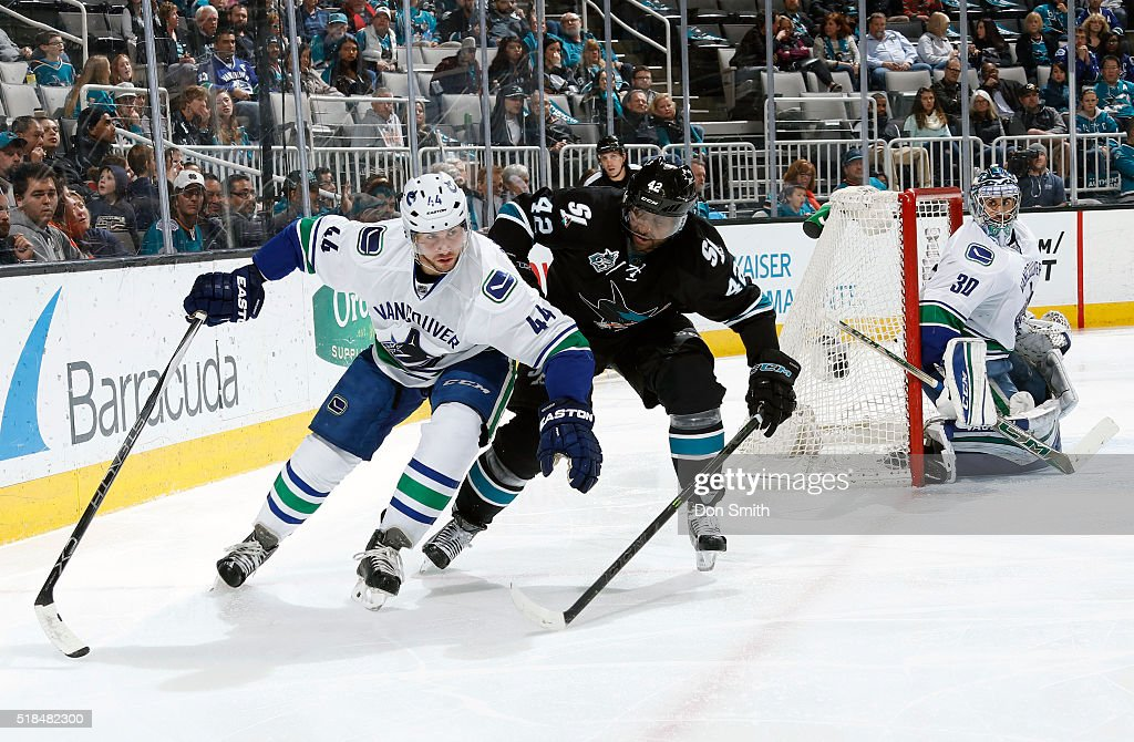 Joel Ward #42 of the San Jose Sharks keeps close defense against Matt Bartkowski #44 of the Vancouver Canucks during a NHL game at the SAP Center at San Jose on March 31, 2016 in San Jose, California.