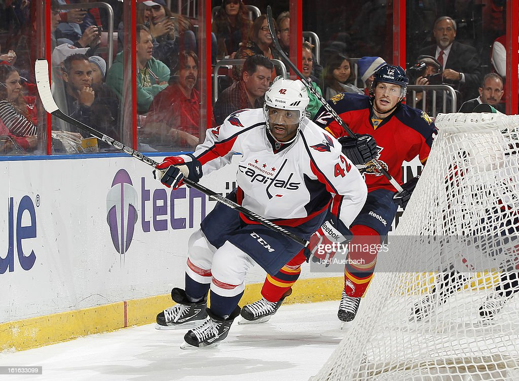 Joel Ward #42 of the Washington Capitals and Jack Skille #12 of the Florida Panthers skate after a loose puck at the BB&T Center on February 12, 2013 in Sunrise, Florida. The Capitals defeated the Panthers 6-5 in overtime.