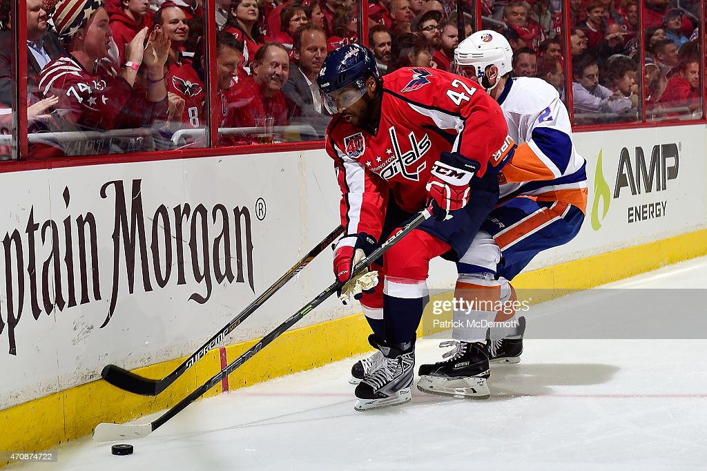 Joel Ward of the Washington Capitals and Nick Leddy of the New York Islanders battle for the puck against the boards during the second period in Game...