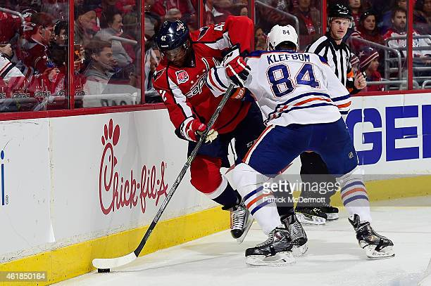 Joel Ward of the Washington Capitals and Oscar Klefbom of the Edmonton Oilers battle for the puck against the boards in the second period during an...