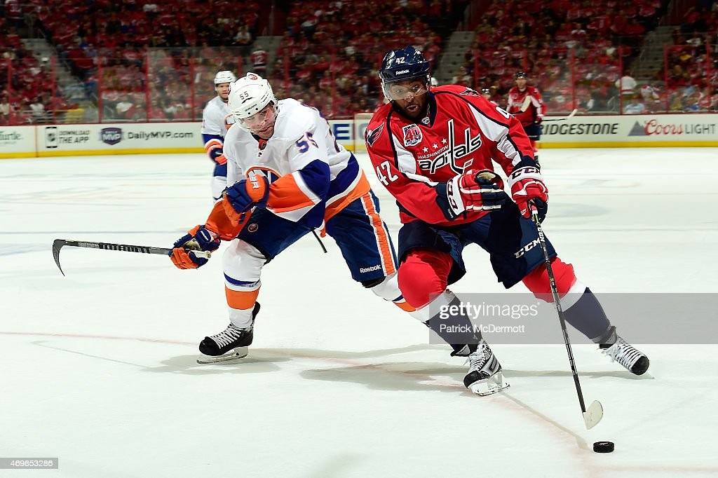 Joel Ward of the Washington Capitals controls the puck against Johnny Boychuk of the New York Islanders during the second period in Game One of the...