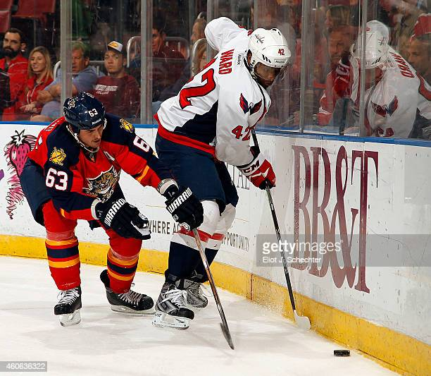 Joel Ward of the Washington Capitals digs the puck out from the boards against Dave Bolland of the Florida Panthers at the BBT Center on December 16...
