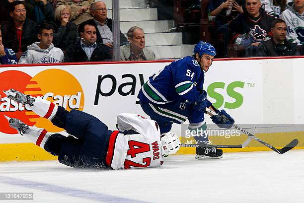 Joel Ward of the Washington Capitals falls to the ice as he tries to check Aaron Volpatti of the Vancouver Canucks during their NHL game at Rogers...