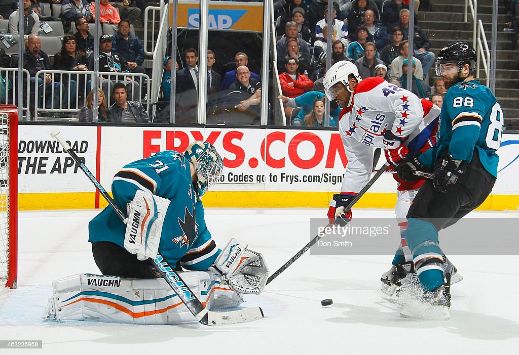 Joel Ward of the Washington Capitals gets the game winning goal in overtime against Antti Niemi and Brent Burns of the San Jose Sharks during an NHL...
