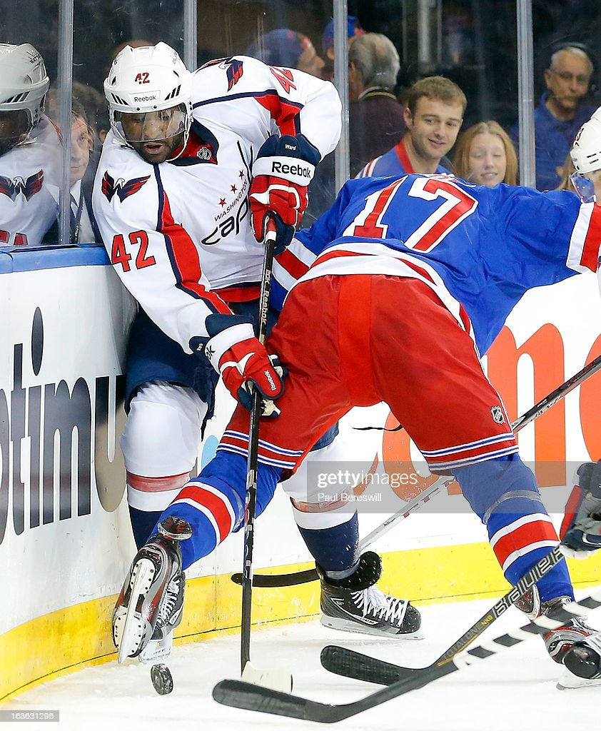 Joel Ward #42 of the Washington Capitals is checked by John Moore #17 of the New York Rangers during the first period in Game Six of the Eastern Conference Quarterfinals during the 2013 NHL Stanley Cup Playoffs at Madison Square Garden on May 12, 2013 in New York City. Rangers won 1-0.