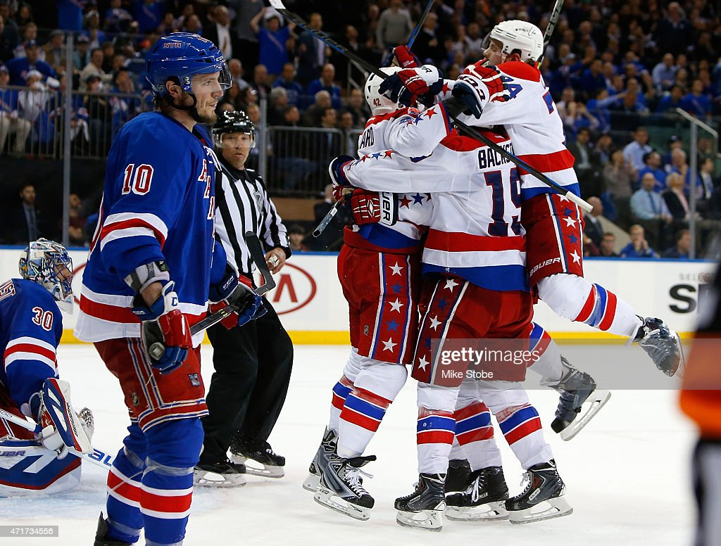 Joel Ward of the Washington Capitals is mobbed by his teamates after scoring the game winning goal at 1958 as Henrik Lundqvist and JT Miller of the...