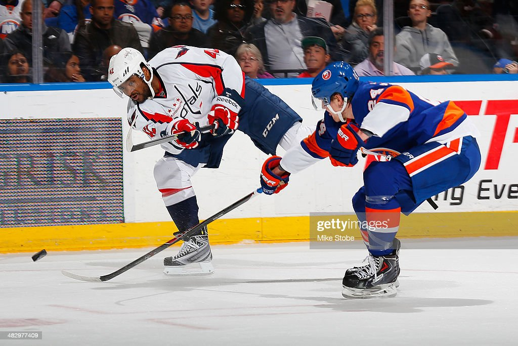 Joel Ward #42 of the Washington Capitals shoots the puck as Kevin Czuczman #24 of the New York Islanders defends him at Nassau Veterans Memorial Coliseum on April 5, 2014 in Uniondale, New York. The Capitals defeated the Islanders 4-3.