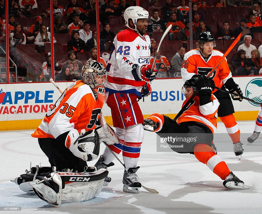 Joel Ward #42 of the Washington Capitals takes the feet out from under <a gi-track='captionPersonalityLinkClicked' href=/galleries/search?phrase=Mark+Streit&family=editorial&specificpeople=636976 ng-click='$event.stopPropagation()'>Mark Streit</a> #32 of the Philadelphia Flyers in front of goalie Steve Mason #35 during the third period of an NHL hockey game at Wells Fargo Center on December 17, 2013 in Philadelphia, Pennsylvania.