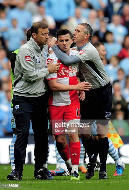 Joey Barton of QPR is restrained by QPR First Team Coach Eddie Niedzwiecki and QPR Goalkeeping Coach Kevin Hitchcock after being shown the red card...