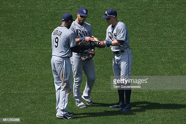 Joey Butler of the Tampa Bay Rays plays rock paper scissors as they celebrate their victory with Kevin Kiermaier and Brandon Guyer during MLB game...