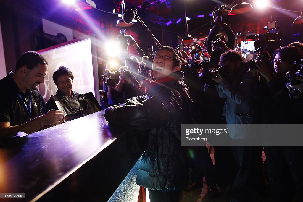 Joey Chiu, 24, center, reacts as he purchases the first Sony PlayStation 4 console during its midnight launch event in New York, U.S., on Friday, Nov. 15, 2013. Sony Corp., poised to release the PlayStation 4 game console this week, is confident it can meet analysts' sales estimates of 3 million units by year-end, exploiting an early advantage over Microsoft Corp.'s Xbox One. Photographer: Victor J. Blue/Bloomberg via Getty Images