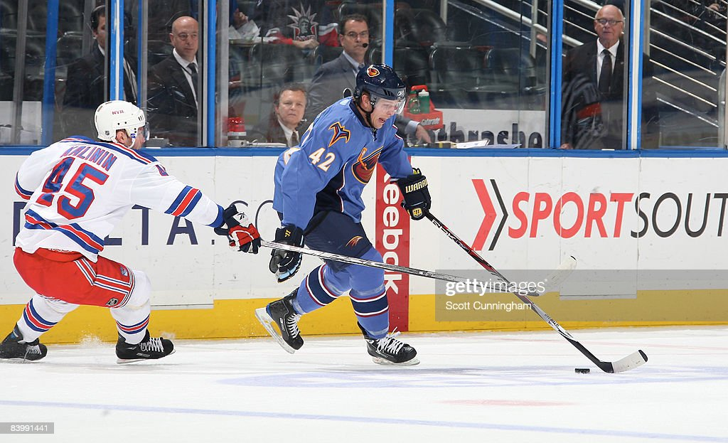 Joey Crabb of the Atlanta Thrashers carries the puck against Dmitri Kalinin of the New York Rangers at Philips Arena on December 10 2008 in Atlanta...