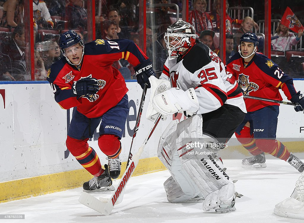 Joey Crabb of the Florida Panthers attempts to take the puck from Goaltender Cory Schneider of the New Jersey Devils in the first period at the BBT...