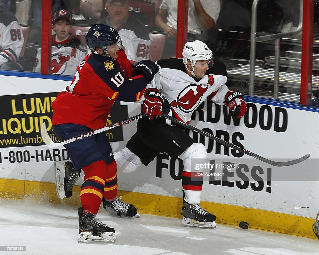 Joey Crabb of the Florida Panthers battles with Andy Greene of the New Jersey Devils for control of the puck in the third period at the BBT Center on...
