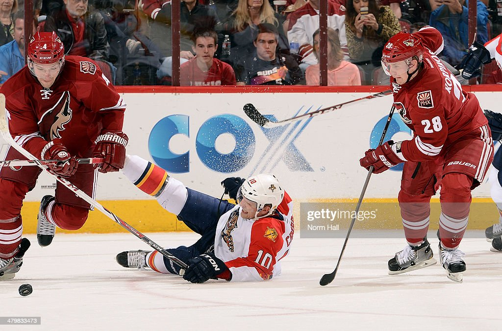 Joey Crabb of the Florida Panthers falls to the ice between Zbynek Michalek and Lauri Korpikoski of the Phoenix Coyotes during the second period at...