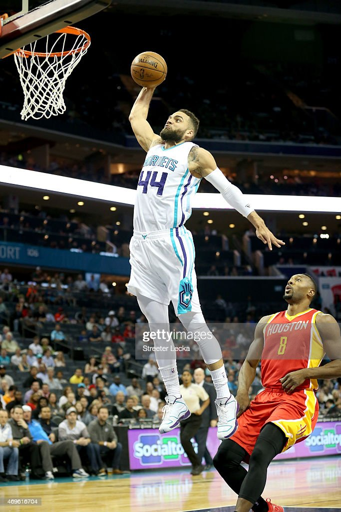 Joey Dorsey of the Houston Rockets watches as Jeff Taylor of the Charlotte Hornets dunks the ball during their game at Time Warner Cable Arena on...