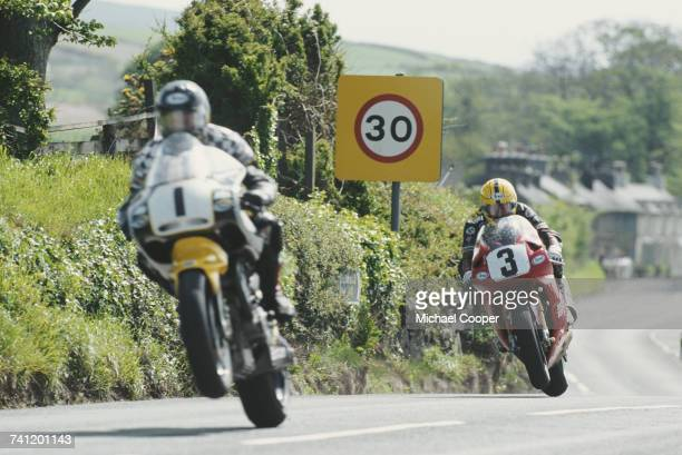 Joey Dunlop of Great Britain and rider of the Honda Britain Honda RC45 chases Shaun Harris on the Britten V1000 during the International Isle of Man...