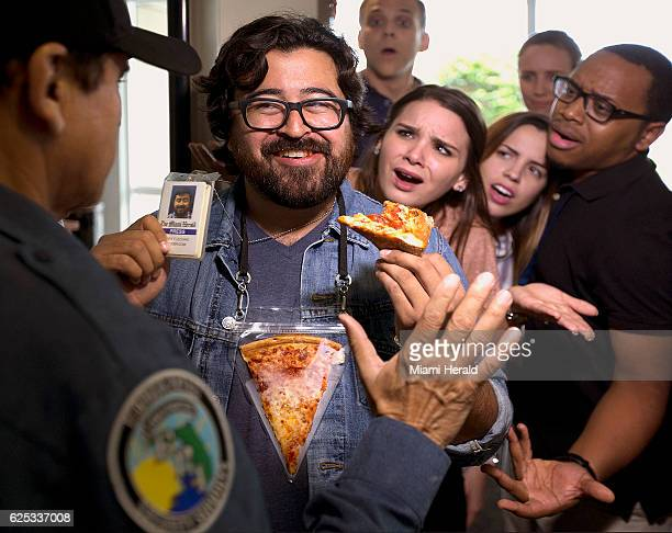 Joey Flechas doesn't let getting into work stand in the way of enjoying his pizza thanks to the Pizza Pouch as he shows his identification to Miami...