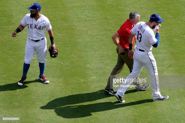 Joey Gallo of the Texas Rangers leaves the game after colliding with Matt Bush of the Texas Rangers while fielding the ball against the Chicago White...