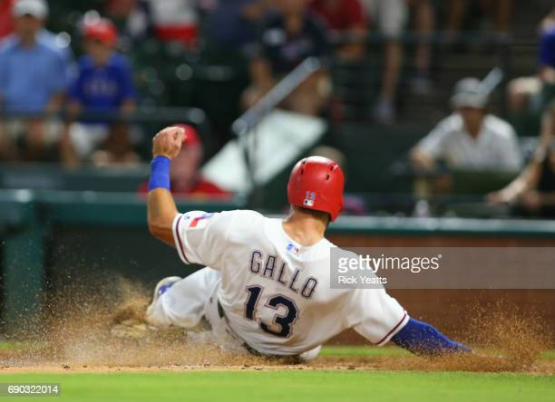 Joey Gallo of the Texas Rangers slides in safe at home plate in the eighth inning against the Tampa Bay Rays at Globe Life Park in Arlington on May...