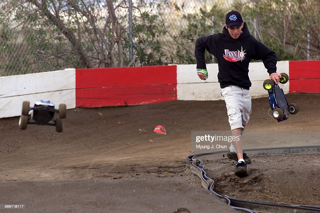 Joey Gerber 14 of Canyon Country helps retrieve a stuck car for a driver during practice runs at the Hot Rod Hobbies off–road track in Saugus Top...