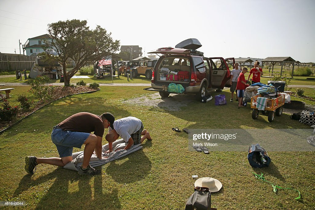 Joey Haywood of Troy, NC. and his son Dawson Haywood fold up the families tent at a campsite before departing the KOA Capmground to comply with the mandatory evacuation orders for Hatteras Island, July 3, 2014 in Rodanthe, North Carolina. A Hurricane warning has been issued for North Carolina's Outer Banks due to approaching Tropical Storm Arthur that is expected to gain strength and become a category 1 hurricane before it passes the area.