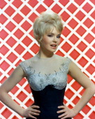 Joey Heatherton US actress dancer and singer poses wearing a dark blueandsilver bodice in a studio portrait against a redandwhite background circa...