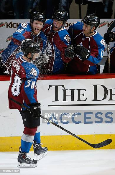 Joey Hishon of the Colorado Avalanche celebrates his first NHL goal and is douses with a water bottle by team captain Gabriel Landeskog of the...