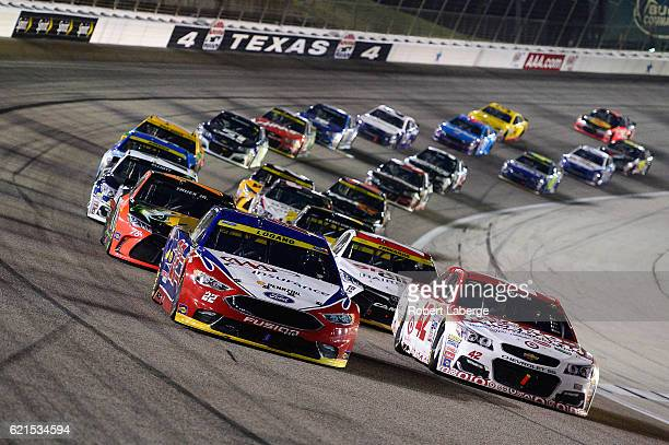 Joey Logano driver of the AAA Ford and Kyle Larson driver of the Target/CocaCola Chevrolet lead the field during the NASCAR Sprint Cup Series AAA...