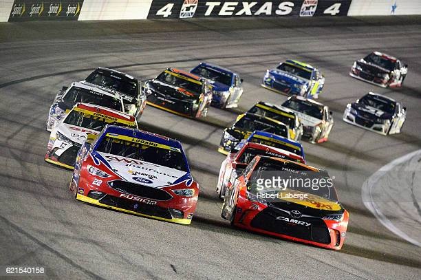 Joey Logano driver of the AAA Ford and Martin Truex Jr driver of the Bass Pro Shops/TRACKER Boats Toyota lead the field during the NASCAR Sprint Cup...