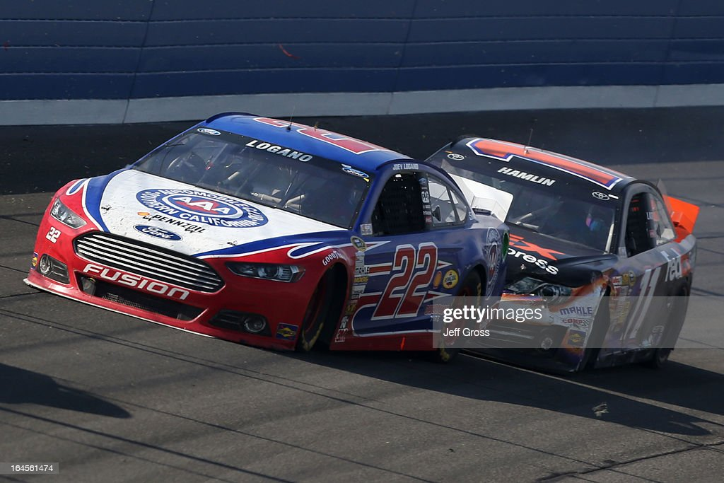Joey Logano, driver of the #22 AAA Southern California Ford, collides with Denny Hamlin, driver of the #11 FedEx Express Toyota, on the the last lap during the NASCAR Sprint Cup Series Auto Club 400 at Auto Club Speedway on March 24, 2013 in Fontana, California.