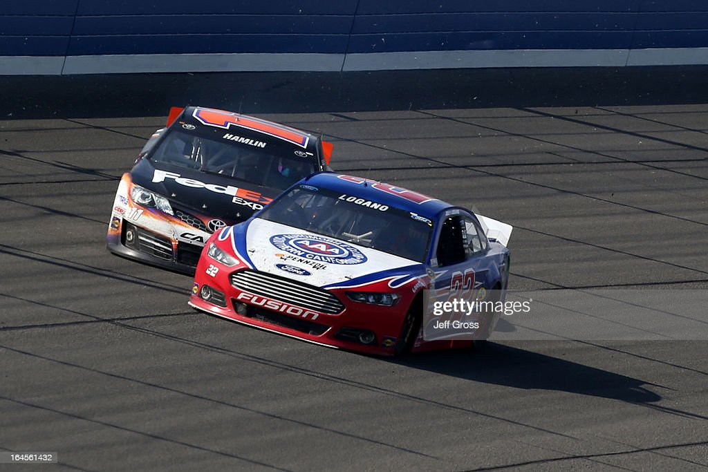 Joey Logano, driver of the #22 AAA Southern California Ford, cuts off Denny Hamlin, driver of the #11 FedEx Express Toyota, in the final laps of the NASCAR Sprint Cup Series Auto Club 400 at Auto Club Speedway on March 24, 2013 in Fontana, California.
