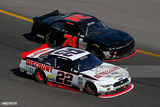 Joey Logano driver of the Discount Tire Ford races against Mike Harmon driver of the Dodge during the NASCAR XFINITY Series Axalta Faster Tougher...