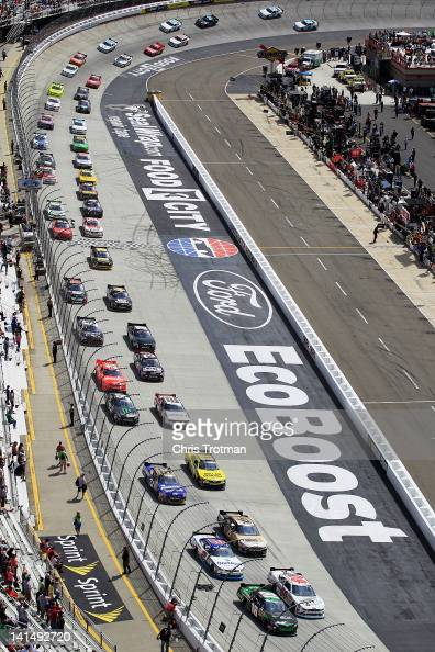 Joey Logano driver of the GameStop Toyota and Trevor Bayne driver of the Roush Fenway Racing Ford lead the pack at the start of the NASCAR Nationwide...