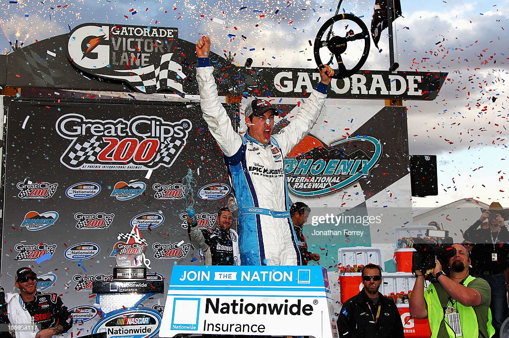 Joey Logano driver of the GameStop/Epic Mickey2 Toyota celebrates in Victory Lane after winning the NASCAR Nationwide Series Great Clips 200 at...