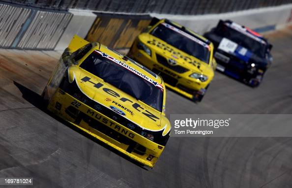 Joey Logano driver of the Hertz Ford leads Brian Vickers driver of the Dollar General Toyota and Trevor Bayne driver of the Ford EcoBoost Ford during...