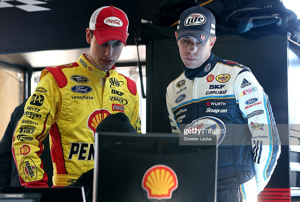 Joey Logano, driver of the #22 Penske Racing Ford, looks at a computer with Brad Keselowski, driver of the #2 Penske Racing Ford, during NASCAR Testing at Charlotte Motor Speedway on January 18, 2013 in Charlotte, North Carolina.