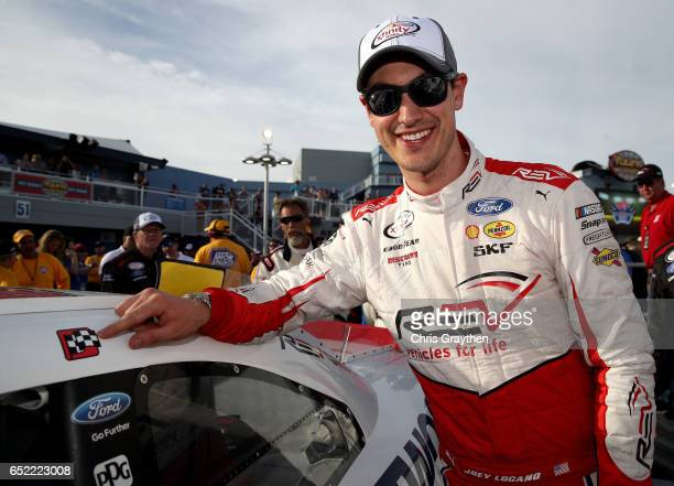 Joey Logano driver of the REV Ford poses with the winner's decal on his car in Victory Lane after winning the NASCAR XFINITY Series Boyd Gaming 300...
