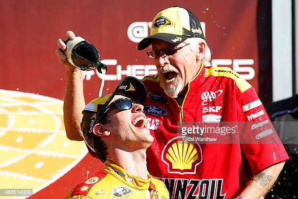 Joey Logano driver of the Shell Pennzoil Ford and a crew member celebrate with champagne after winning the NASCAR Sprint Cup Series CheezIt 355 at...