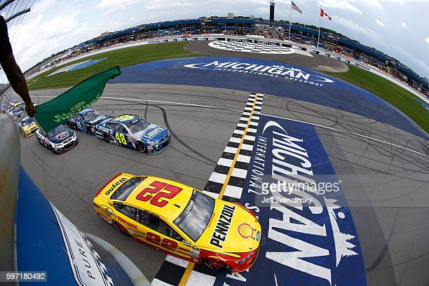 Joey Logano driver of the Shell Pennzoil Ford and Jimmie Johnson driver of the Lowe's Chevrolet lead the field to the green flag during the NASCAR...