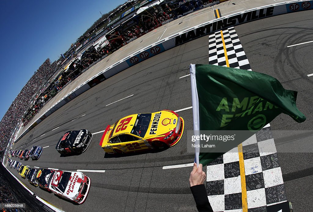Joey Logano, driver of the #22 Shell Pennzoil Ford, and Ryan Newman, driver of the #31 Quicken Loans Chevrolet, lead the field to start the NASCAR Sprint Cup Series STP 500 at Martinsville Speedway on March 29, 2015 in Martinsville, Virginia.