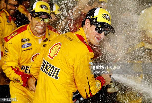 Joey Logano driver of the Shell Pennzoil Ford celebrates with champagne in Victory Lane after winning the NASCAR Sprint Cup Series IRWIN Tools Night...