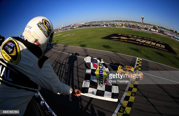 Joey Logano driver of the Shell Pennzoil Ford crosses the finish line to win the NASCAR Sprint Cup Series Hollywood Casino 400 at Kansas Speedway on...