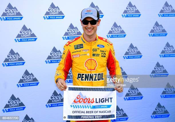 Joey Logano driver of the Shell Pennzoil Ford poses with the Coors Light Pole Award after qualifying in the pole position for the Monster Energy...