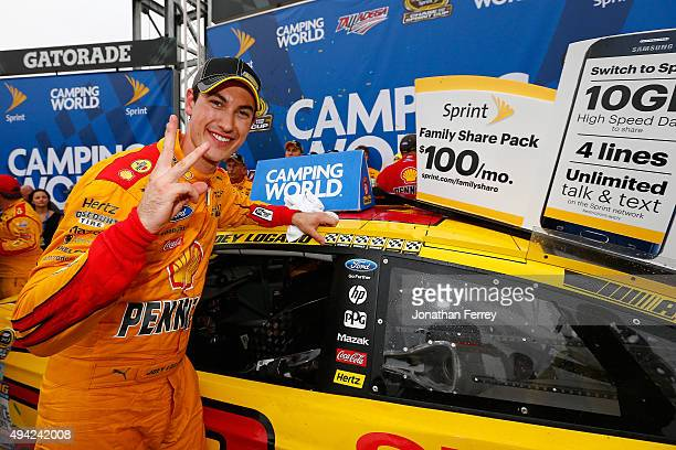 Joey Logano driver of the Shell Pennzoil Ford poses with the winner's decal in Victory Lane after winning the NASCAR Sprint Cup Series...