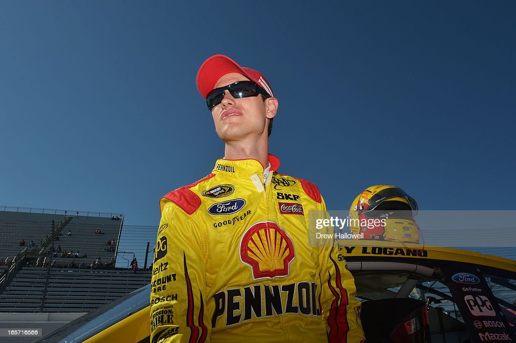 Joey Logano, driver of the #22 Shell Pennzoil Ford, stands on the grid during qualifying for the NASCAR Sprint Cup Series STP Gas Booster 500 on April 5, 2013 at Martinsville Speedway in Ridgeway, Virginia.