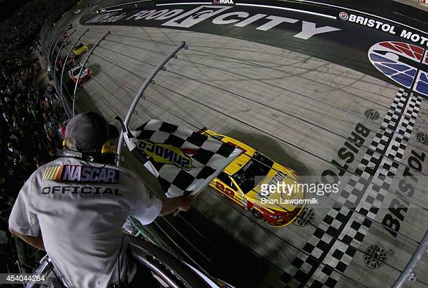 Joey Logano driver of the Shell Pennzoil Ford takes the checkered flag to win the NASCAR Sprint Cup Series Irwin Tools Night Race at Bristol Motor...